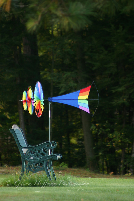 Rainbow colored whirlygig and bench. Summer