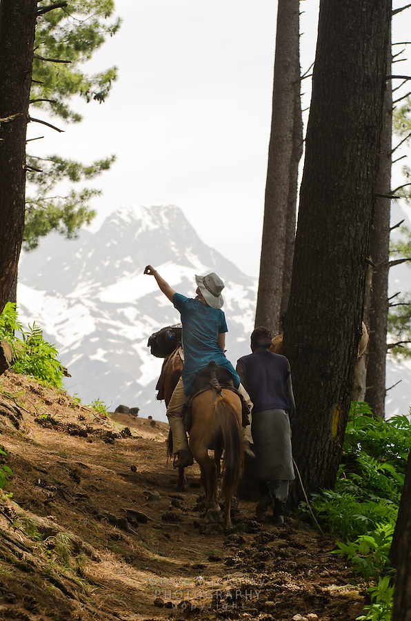 Western tourist on horseback with guide in the stunning alpine wonderland above Naranag, Kashmir, India.
