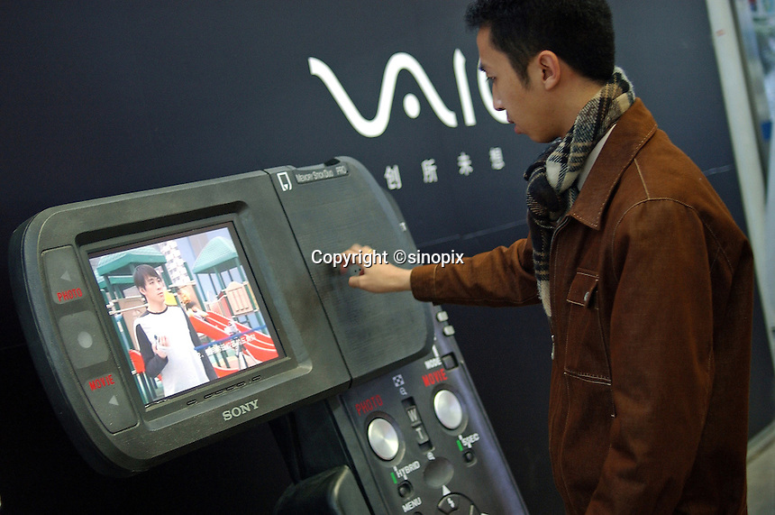 A man checks out the giant model of Sony VAIO digital camera at a shopping mall in Guangzhou, China..02-FEB-05