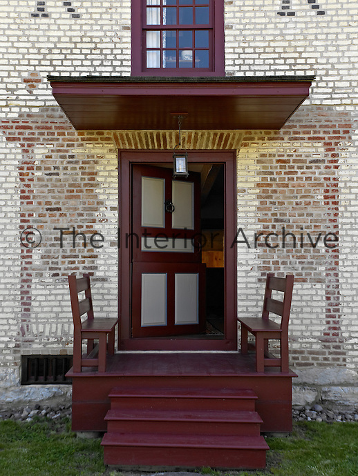 The ghost of past porches is etched into the brick facade around the front door, which is reached by a simple 'stoep'