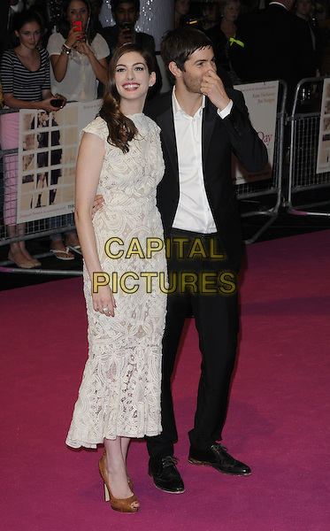 "ANNE HATHAWAY (in Alexander McQueen) & JIM STURGESS.""One Day"" UK premiere, Vue Westfield cinema, Westfield Shopping Centre, London, England..August 23rd, 2011.full length white sleeveless crochet lace dress brown hazelnut whipstitch peep toe shoes white embroidered shirt black suit hand holding nose.CAP/CAN.©Can Nguyen/Capital Pictures."