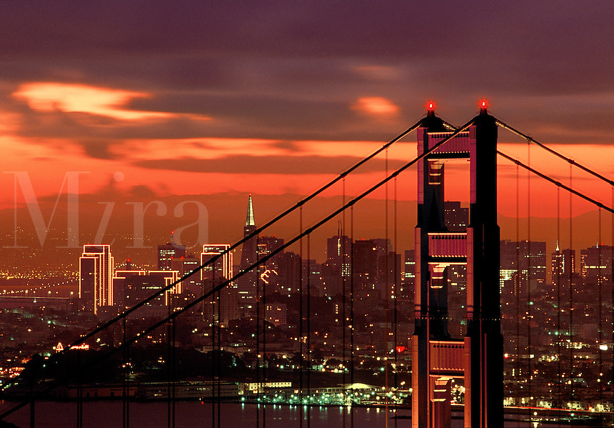Golden Gate Bridge Tower at sunrise with skyline beyond San Francisco California USA