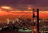 Golden Gate Bridge Tower at sunrise with skyline beyond San Francisco California USA