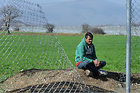 Pictured: A migrant man sits on the soil Tuesday 01 March 2016<br />Re: Thousands of migrants, still stranded at the Greek FYRO Macedonian border in Idomeni, Greece