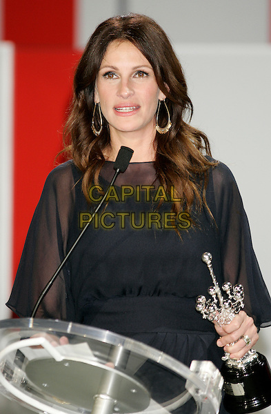 "JULIA ROBERTS.""Eat Pray Love"" premiere and Donostia Award during the 58th International Film Festival San Sebastian, San Sebastian, Spain, September 20th, 2010.half length black sheer dress award trophy holding  gold bracelets see thru through podium microphone speaking.CAP/PE.©Peter Eden/Capital Pictures."