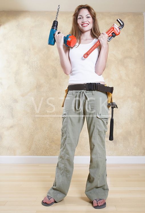 Portrait of smiling woman holding power drill and wrench