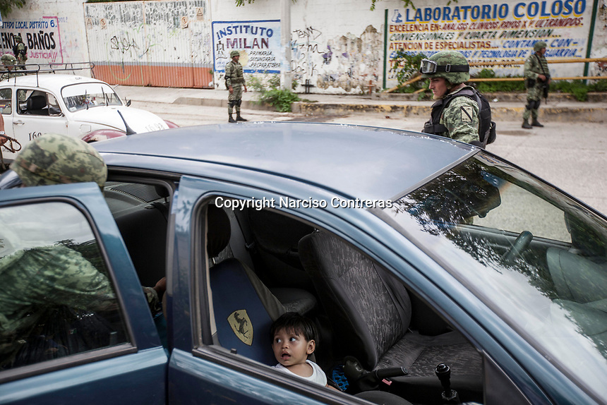 June 17, 2018: A young kid reacts as Mexican army soldiers look for drugs and weapons at a flying check point set up at La Sabana, a violence-plagued neighbourhood in the outskirts of Acapulco, Guerrero. A juncture of security forces, among them military, marines, federal police and local police joined under one-command to fight crime violence in the region.