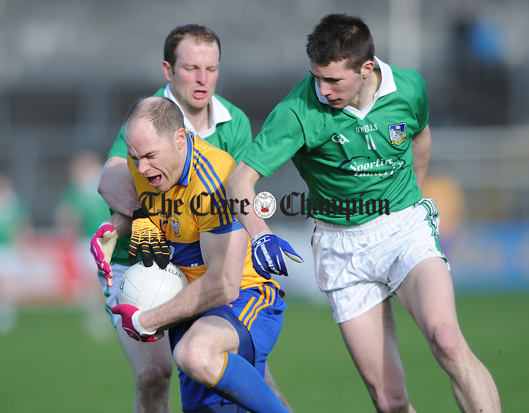 Michael O Shea of Clare in action against Lorcan O Dwyer and Eoin O Connor of Limerick during their National League game at Cusack Park. Photograph by John Kelly.