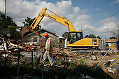 New Orleans, Louisiana.May 25, 2006..Demolition teams work at leveling as many as 6,000 homes in St. Bernard's Parish damaged by hurricane Katrina in August of 2005...FEMA is offering to destroy home for free up until June 30, 2006. About 12 homes are being demolished a day so far. ..Workers are outfitted in special clothing and masks and water is poured on the debris as the homes have asepses. The water is to keep down the asepses fumes..