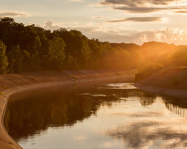 August 6, 2016. Flint, Michigan.<br />  Sunset on the Flint River. <br />  In April 2014, the city of Flint switched its water source from the Detroit Water and Sewerage Department to using the Flint River in an effort to save money. When the switch occurred, the city failed to have corrosion control treatment in place for the new water. This brought about a leaching of lead from pipes into the water, increasing the lead content in the drinking water to levels far above legal limits. After independent sources brought this to light, the city admitted the water was unsafe and legal battles have ensued between resident and the local and state governments.