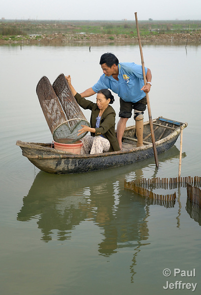 Nguyen Xuan Hien, who lost a leg to a landmine, harvests shrimp from a pond with help from his wife, Le Van Thoan, in Bo Trach, Vietnam.