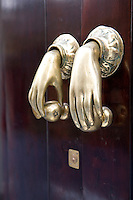 A pair of brass cupboard handles in the shape of a woman's hands