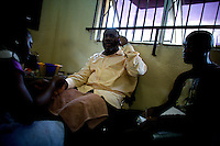 """Actors Guild of Nigeria president Ejike Asiegbu has a manicure done while one of his layers from the guild's counsel office passes him calls to answer at the """"Downtown beauty salon"""" where several Nollywood stars frequently have their hair styled by head hair dresser Agnes Adamson and her staff in Lagos, Nigeria on Friday March 27 2009..Currently the most requested hair styles at the salon are """"Take a bow"""" and Crazy Alia""""...Currently, Nigerian films outsell Hollywood films in Nigeria and many other African countries..Nollywood is a nascent film industry in Nigeria, growing up within the last two decades to become the third largest film industry on the planet, behind the United States and Indian film industries. Nigeria has a US$250 million movie industry, churning out some 200 videos for the home video market every month."""