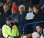 """A fan with a sign behind Craig Whyte in the stand reading """"We don't need Jelavic"""""""