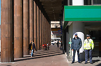 On the Plaza Independencia, Independence Square: a colonnade with a woman walking and to security guards outside a bank building. Montevideo, Uruguay, South America
