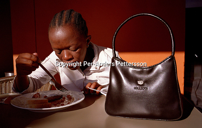 GABORONE, BOTSWANA - FEBRUARY 25: Alice Manthe, age 31, eats breakfast in the Metcourt Hotel a day before the Miss HIV Stigma Free Botswana competition held annually in the international convention center on February 24, 2005 in Gaborone, Botswana. Twelve HIV positive women selected from around the country were trained how to walk, make a speech during an intense week of preparations. The pageant is held to make the people of Botswana more aware of HIV-Aids, and stop the stigma that makes people afraid of being tested and acknowledge their status. Botswana has a population of about 1,7 million people and about 38 percent are believed to be infected with the virus. Alice has been on antiretroviral drugs since 2002 and she volunteers for an Aids organization n Gaborone. .(Photo: Per-Anders Pettersson/Getty Images)..