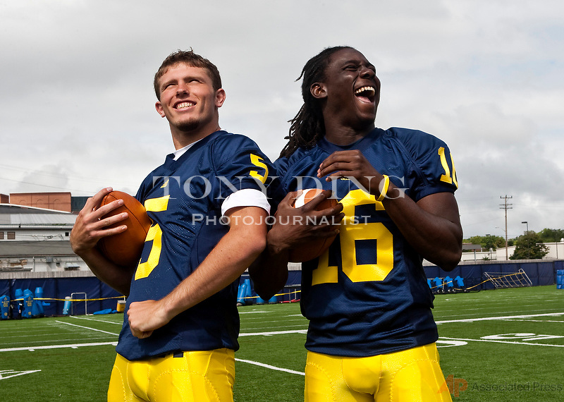 Michigan freshman quarterbacks Tate Forcier (5) and Denard Robinson (16) joke around while being photographed during the school's annual football media day, Sunday, Aug. 23, 2009, in Ann Arbor, Mich. (AP Photo/Tony Ding)