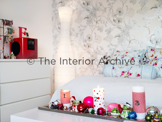 Rie Bidstrup's daughter has decided to decorate her wall with wallpaper from Designers Guild. An advent candle holder decorated with lots of colourful balls has been placed on the table in front of the bed
