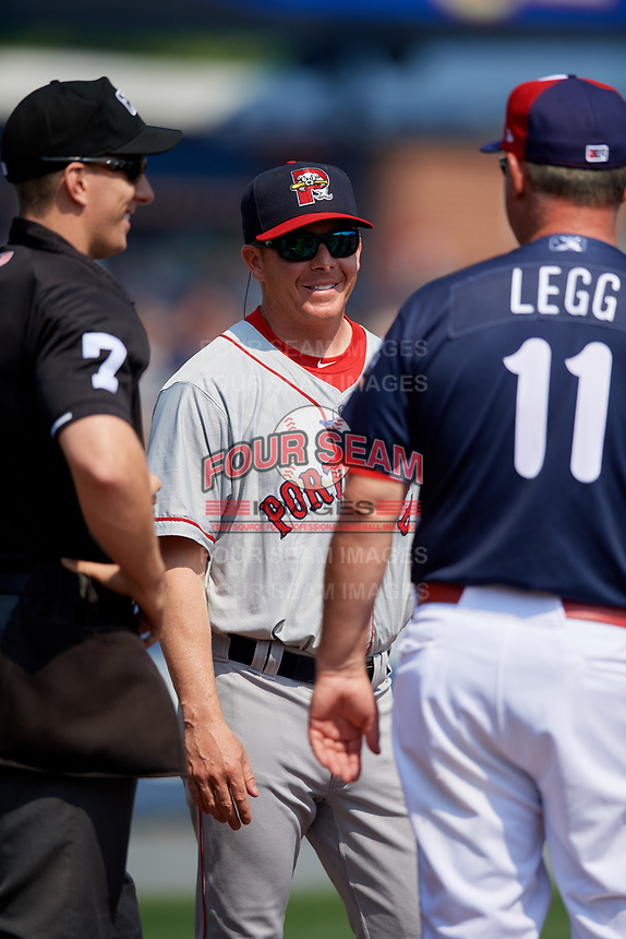 Portland Sea Dogs manager Darren Fenster (23) meets with manager Gregg Legg (11) and home plate umpire Derek Thomas prior to the first game of a doubleheader against the Reading Fightin Phils on May 15, 2018 at FirstEnergy Stadium in Reading, Pennsylvania.  Portland defeated Reading 8-4.  (Mike Janes/Four Seam Images)
