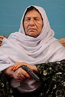 Commander Kaftar poses with her revolver at a the safe house she now lives in on the outskirts of Pul-e Khumri, a small city in Bahglan province in Afghanistan. <br /> The only known female Mujahideen commander, Kaftar, was once the leader of a 600-strong armed force. Today she can&rsquo;t even leave the safe house where she is staying as a guest along with her granddaughter. Her enemies, mostly from the neighboring village, are looking for her to settle an old score. According to local accounts, her husband failed to avenge the murder of a relative &ndash; Bibi, as she is called by her eight children, took matters into her own hands and soon after enlisted with the Jamiyat-e-Islami forces of Ahmad Shah Massoud&rsquo;s forces at the height of the Soviet invasion of Afghanistan in the early 80&rsquo;s. Born in Bahglan province, Kaftar is proud to have never surrendered to the Taliban &ndash; in fact, her area of operations never fell to the militants onslaught. Like many other Jihadi commanders, Kaftar surrendered her weapons as part of the UN Disbandment of Illegal Armed Groups program (DIAG) &ndash; however, she kept some small arms for herself and her personal guards. One of these weapons is her Russian-made Makarov pistol, which she always carries on a holster under her shoulder. <br /> Like many other warlords (and former Mujahideen) in Afghanistan, Kaftar used the power of the gun for extortion and self-enrichment. Several residents of her native village of Khoza claim that she is responsible for at least ten deaths along with demanding tax money and extortion from the locals in order to fund her operations. Like many other warlords in Afghanistan, the central and local governments have not made any effort to bring her to justice.