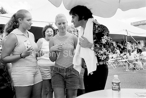 Memphis, Tennessee<br /> USA<br /> August 14, 2002<br /> <br /> Often more interesting then the Elvis impersonators were the Elvis fans who treated the impersonators like Elvis himself. They asked for autographs, photos and addressed all impersonators by the name of Elvis. This marked the 25th anniversary of Mr. Presley's death.