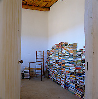 Books stacked horizontally in the bedroom defy the need for conventional shelving