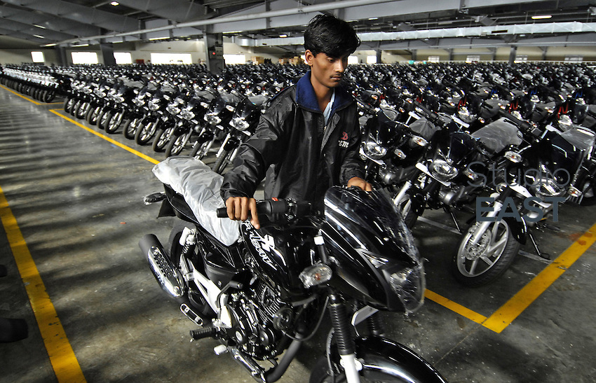 An employee pushes a Bajaj Pulsar motor bike, manufactured by Bajaj Auto Ltd, past a line of other motorcycles parked in a storage warehouse of the company's factory in Chakan, near Pune, about 150 km East of Mumbai, India, on Thursday, August 9, 2007. French car maker Renault and India's second largest two-wheeler maker Bajaj Auto, are mulling a joint venture to make a new $3,000 car in India. Photo by Abhijit Bhatlekar/Pictobank