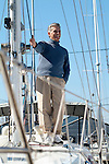 Man standing on deck of sail boat in marina