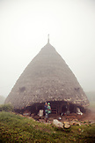 INDONESIA, Flores, Wae Rebo Village, a woman and her baby stand in front of her traditional thatched home called Mbaru Niang
