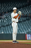 Texas Longhorns relief pitcher Cole Quintanilla (34) looks to his catcher for the sign against the Arkansas Razorbacks in game six of the 2020 Shriners Hospitals for Children College Classic at Minute Maid Park on February 28, 2020 in Houston, Texas. The Longhorns defeated the Razorbacks 8-7. (Brian Westerholt/Four Seam Images)