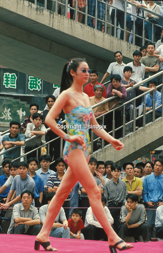 Mostly men crowd around a women's swim wear fashion show in Shenzhen. An average gender inbalance 118 males to 100 females caused by the Chinese Governments One Child Policy and the  preference for boys means that there is a shortage of women in China.
