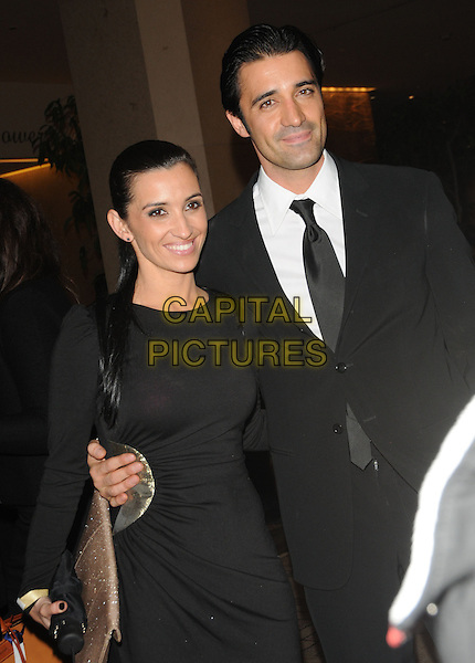 CAROLE & GILLES MARINI.Leaving the 67th Golden Globes held at The Beverly Hilton Hotel in Beverly Hills, California, USA..January 17th, 2010 .departures half length black suit dress  married husband wife.CAP/DVS.©Debbie VanStory/Capital Pictures
