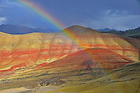 A rainbow arc forms in front of a section of the Painted Hills National Monument in central Oregon.