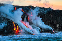 At dawn on the 30th anniversary of Kilauea's eruption, lava flows into the ocean along the border of Hawai'i Volcanoes National Park on the Big Island.