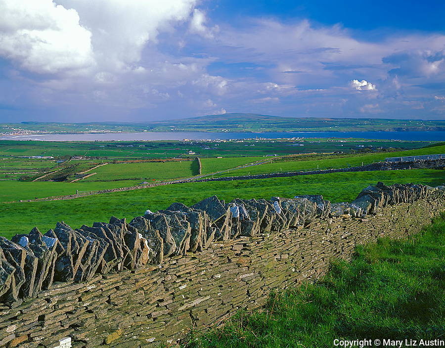 County Clare, Ireland<br /> Clearing storm clouds over stone fences and green hillsides near the village of Lahinch on Liscannor Bay