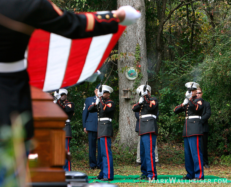 While Marines lift and prepare to fold the American flag from the coffin of Lance Cpl. Daniel Chaires on Thursday, Nov. 2, 2006, members of the U.S. Marine Corps honor guard fire a rifle salute during the graveside service for the Chaires, Fla., native.  (Mark Wallheiser/TallahasseeStock.com)