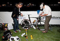 13 MAR 2010 - ABU DHABI, UAE - Philip Graves prepares his bike in transition, with the assistance of his father Martin Graves, before the start of the Abu Dhabi International Triathlon .(PHOTO (C) NIGEL FARROW)
