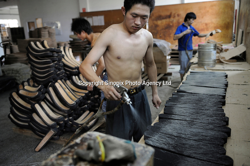 Laborers spray glue for office chairs at a Taiwan-capital furniture factory in Huizhou, Guangdong, China..