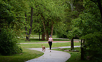 A resident walks alongside a dog Friday, May 15, 2020, on the trail in Gulley Park in Fayetteville. The city has recorded a significant increase in trail users since the coronavirus pandemic hit in mid-March. The trail near Gulley Park has had a monthly average of about 25,000 users, compared to about 14,000 at the same time last year. Visit nwaonline.com/200516Daily/ for today's photo gallery.<br /> (NWA Democrat-Gazette/Andy Shupe)