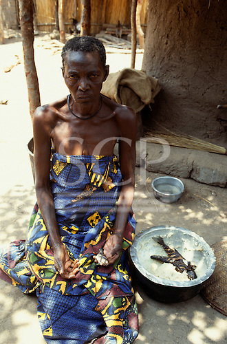 Izinga, Tanzania. Emaciated old woman with bowl of cereal paste with fish outside a mud walled hut.