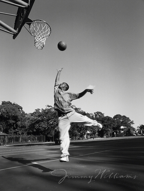 A young african-american boy gets air while playing basketball at his school