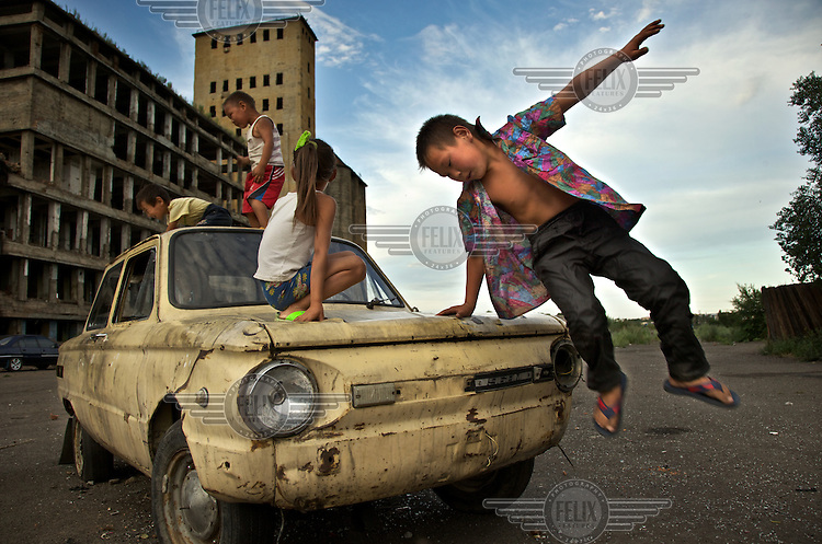EMBARGOED UNTIL DEC 12, 2011. ..Children play on a beaten Lada car in front of an abandoned factory in Kyzyl, capital of Tuva Republic, southern Siberia, Russia. The factory used to process grain during Soviet times. Cut off from air and train traffic, this is one of Russia's poor regions.