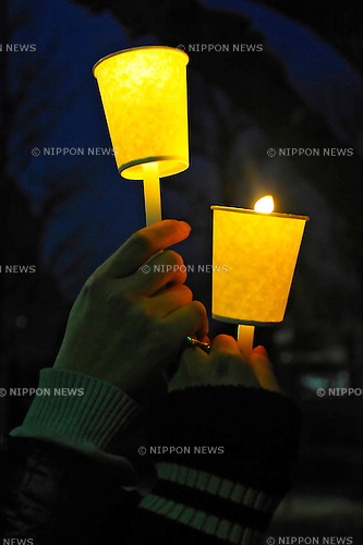 "Tokyo, Japan - March 11: Two people held a candle and hands in front of the Diet Building at Chiyoda, Tokyo, Japan as a demonstration against nuclear power on March 11, 2012. More than 10,000 people held the candles and hands of next people to make a ""Human Chain."" As this day was one year anniversary of Great East Japan Earthquake and Tsunami, there were many demonstrations held in the city."