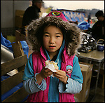 Mika Suzuki, 10, eats Japanese sweets made by volunteers in a shelter in Minamisanriku, Miyagi, in one month after the earthquake and tsunami. The coast side of Minamisanriku was protected by the eight-meter-high water gate after the tsunami of 5 meters height in 1960 that killed 41 people. On March 11, 2011, the wave height of 15 meters (49 feet) went over the water gate and swallowed the whole town. The tsunami destroyed 70% of the 5600 houses in the town. Her house was also washed away. When the tsunami swallowed her town, she was in the school on the hill. The teachers called all students and counted the number of the students. The teachers decided not to move from the hill and stay over a night. Mika stayed up all night with other students and teachers. &quot;We had only three candles to spend a night,&quot; she said. &quot;It was so cold and scary.&quot; The following day, his father walked through a mountain and reached the school to find Mika. &quot;I was so relived that my father showed up,&quot; Mika said. They walked back together through a mountain and reunited with other members of family. <br /> On May 11, 2011, the earthquake of magnitude 9.0, the biggest earthquake in the history of Japan and the fourth biggest earthquake in the world after year 1900, shocked the Tohoku area of Japan. In about 30 minutes, devastating tsunami reached, affecting the coastline with a length of 500 km (310 miles). The tsunami wave height of 39 meters (128 feet) was recorded in a port town in Tohoku. The tsunami swallowed villages along the coast and washed away all houses. The earthquake and tsunami killed more than 15,800 people, and still more than 3,500 people are missing.