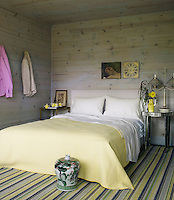 The pastel shade of the bed cover and striped rug complements the grey limewash of the wall cladding in the bedroom