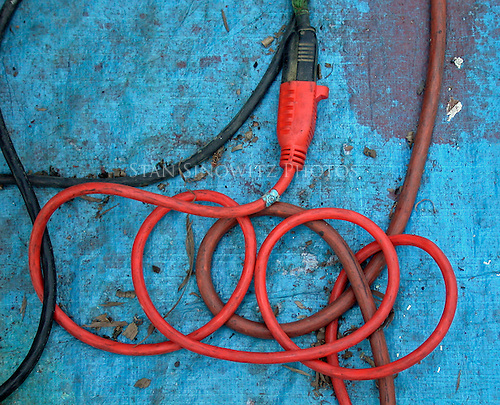 Red electrical wire on a blue tarp in a Boatyard plugged into a black cord which is plugged into a brown cord.