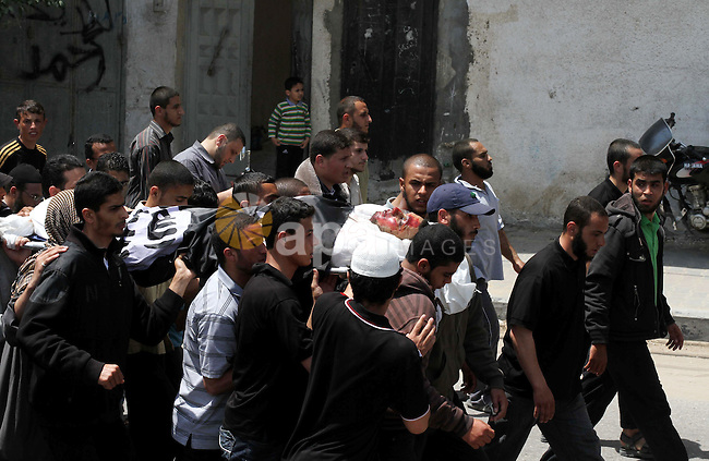 Palestinian mourners carry the body of Haitham Al-Mes-hal, who relatives said belonged to a militant Jihadist Salafi organisation, during his funeral in Gaza City April 30, 2013. Israel on Tuesday launched its first targeted attack on a militant in Gaza since a war in November, killing the Palestinian jihadist in an air strike that put further strain on a five-month-old ceasefire. Photo by Ashraf Amra