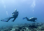 A pair of divers glide over the rubble-strewn reef at Monad Shoal, where we have gone in hopes of seeing the famed thresher sharks.  (At Monad Shoal, Central Visayas, the Philippines)