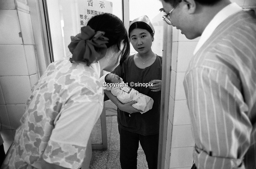A mother and father are presented with their son at the Shenzhen no2 hospital, Shenzhen, China. China's one-child policy has resulted in a nation where boys outnumber girls by almost 20 in every hundred.<br /> Jun 1999<br /> <br /> photo by Richard Jones / Sinopix