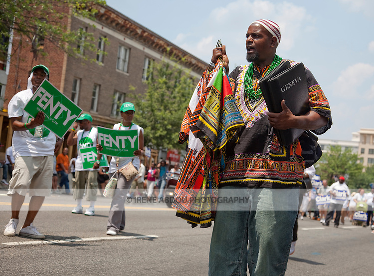 Supporters of Mayor Adrian M. Fenty head up the parade at the 2010 DC Caribbean Carnival in Washington, DC.  In the foreground, a man sells Carribean-style shirts.
